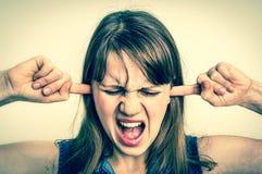 Vrouw die haar oren tegen hevig lawaai behandelen te beschermen royalty-vrije stock fotografie