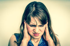 Vrouw die haar oren tegen hevig lawaai behandelen te beschermen stock afbeelding
