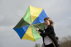Vrouw die haar paraplu op een winderige dag worstelen te houden Royalty-vrije Stock Afbeeldingen