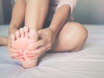 vrouw die haar pijnlijke die voet, rood masseren op pijngebied wordt hallo-aangestoken stock foto