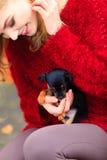 Vrouw die haar puppyhond embrancing Stock Afbeeldingen