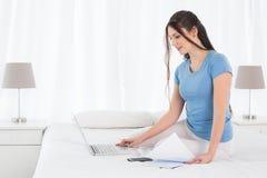 Vrouw die haar rekeningen online met laptop in slaapkamer betalen Royalty-vrije Stock Foto's