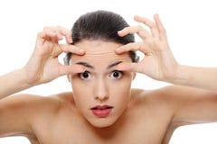 Vrouw die haar rimpels controleert op haar voorhoofd Stock Afbeeldingen