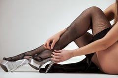 Vrouw die haar schoenen opstijgt Stock Afbeelding