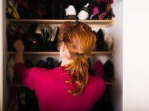 Vrouw die haar schoenen organiseren stock fotografie