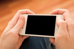 Vrouw die haar smartphone binnen gebruiken Royalty-vrije Stock Afbeeldingen
