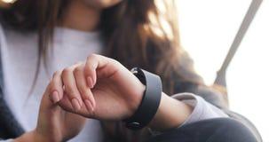 Vrouw die haar smartwatchapparaat openlucht, met een vinger met behulp van die gebaren maken zonnig weer Wearable technologie is  stock video