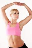 Vrouw die haar spieren uitrekt terwijl het uitoefenen Royalty-vrije Stock Afbeeldingen