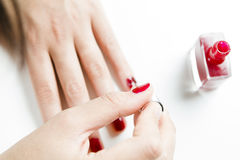 Vrouw die haar spijkers met rood nagellak schilderen Royalty-vrije Stock Foto's
