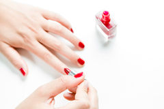 Vrouw die haar spijkers met rood nagellak schilderen Royalty-vrije Stock Afbeeldingen