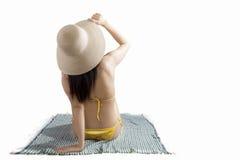 Vrouw die haar strohoed op mat houden Stock Afbeeldingen
