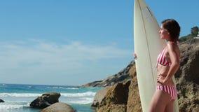 Vrouw die haar surfplank houden aangezien zij het water bekijkt stock videobeelden