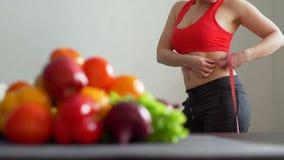 Vrouw die haar Taille meten dichtbij Vruchten en Veggies stock video