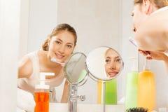 Vrouw die haar die tanden borstelen in badkamersspiegel worden gezien stock foto