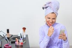 Vrouw die haar tanden borstelen en op de telefoon spreken Stock Afbeeldingen