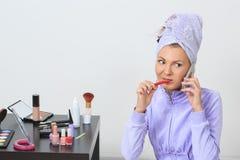 Vrouw die haar tanden borstelen en op de telefoon spreken Stock Fotografie