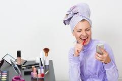 Vrouw die haar tanden borstelen en op de telefoon spreken Stock Foto