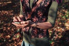 Vrouw die haar telefoon in het park met behulp van Royalty-vrije Stock Foto