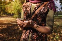 Vrouw die haar telefoon in het park met behulp van Royalty-vrije Stock Afbeeldingen