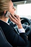 Vrouw die haar telefoon met behulp van terwijl het drijven van de auto stock foto's