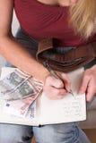 Vrouw die haar uitgaven neerschrijft stock fotografie