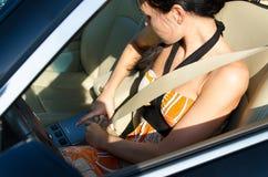 Vrouw die haar veiligheidsgordel aanhaalt stock fotografie
