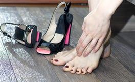 Vrouw die haar vermoeide voeten masseren stock fotografie