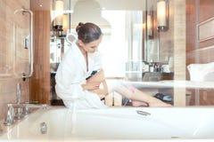 Vrouw die haar verwijderen door haar benen in badkamers van hotel te scheren royalty-vrije stock afbeeldingen