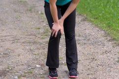 Vrouw die haar Verwonde Knie houden terwijl het Uitoefenen Royalty-vrije Stock Foto