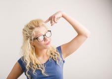 Vrouw die haar vinger richten op haar hoofd stock afbeeldingen