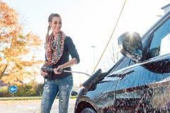 Vrouw die haar voertuig in zelfbedieningsautowasserette schoonmaken stock foto's