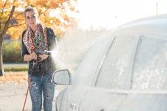 Vrouw die haar voertuig in zelfbedieningsautowasserette schoonmaken stock afbeeldingen