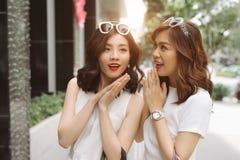 Vrouw die in haar vriendenoren fluisteren Twee opgewekte vriendenshoppi stock foto
