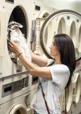 Vrouw die haar wasserij in laundromat doen Stock Afbeeldingen