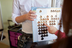 Vrouw die haarkleur kiezen van palet bij salon stock afbeelding