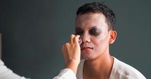Vrouw die Halloween-make-up op man gezicht toepassen stock videobeelden