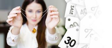 Vrouw die halsband met gele saffier, verkoop houden van juwelen Royalty-vrije Stock Foto's