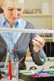 Vrouw die halsband in workshop creëren Stock Foto
