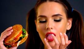 Vrouw die Hamburger eet Het meisje wil snel voedsel eten Stock Fotografie