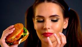Vrouw die Hamburger eet Het meisje wil snel voedsel eten stock afbeelding