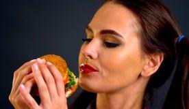 Vrouw die Hamburger eet Het meisje wil snel voedsel eten royalty-vrije stock afbeeldingen