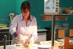 Vrouw die Hamburger in keuken maken stock fotografie