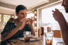 Vrouw die hamburger met vriend hebben bij restaurant Royalty-vrije Stock Afbeeldingen