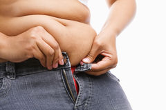 Vrouw die hand probeert aan ritssluiting haar jeans Stock Foto