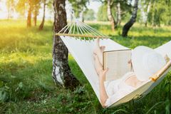 Vrouw die in hangmat in openlucht rusten Ontspan en lezing het boek Royalty-vrije Stock Foto
