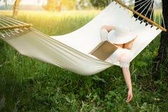 Vrouw die in hangmat rust In openlucht het slapen Stock Afbeeldingen