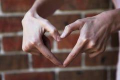 Vrouw die hartvorm met haar handen vormt royalty-vrije stock fotografie