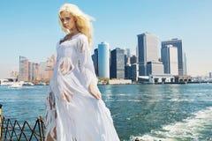 Vrouw die haveloze kleding met de stad op de achtergrond dragen Royalty-vrije Stock Foto's