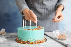 Vrouw die heerlijke verjaardagscake met kaarsen verfraaien bij lijst stock fotografie