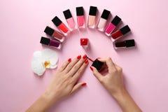Vrouw die helder nagellak op kleurenachtergrond toepast stock foto